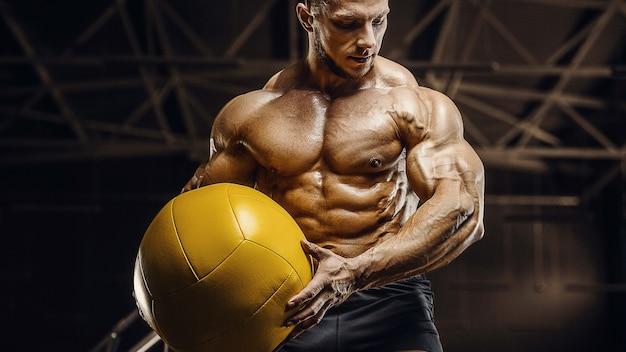Homens bonitos e atléticos treinando músculos com exercícios de fitness com bola e conceito de musculação