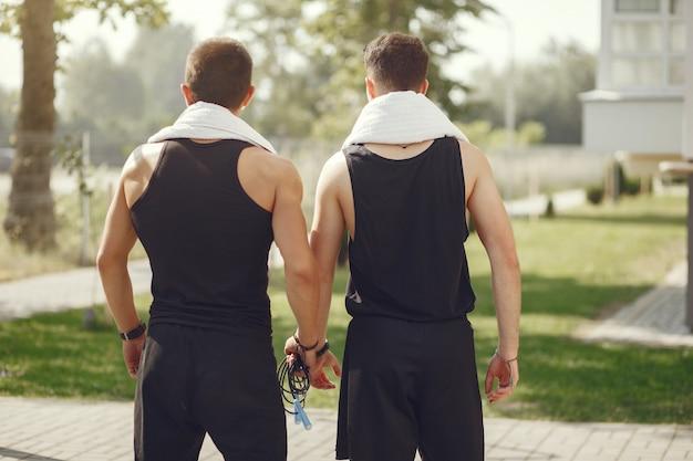 Homens bonitos em uma roupa de esportes em pé em um parque