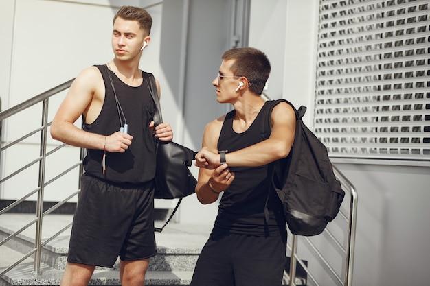 Homens bonitos em uma roupa de esportes em pé em uma cidade
