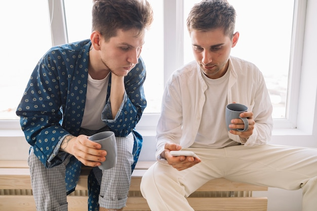 Homens bonitos olhando no celular segurando a xícara de café na mão