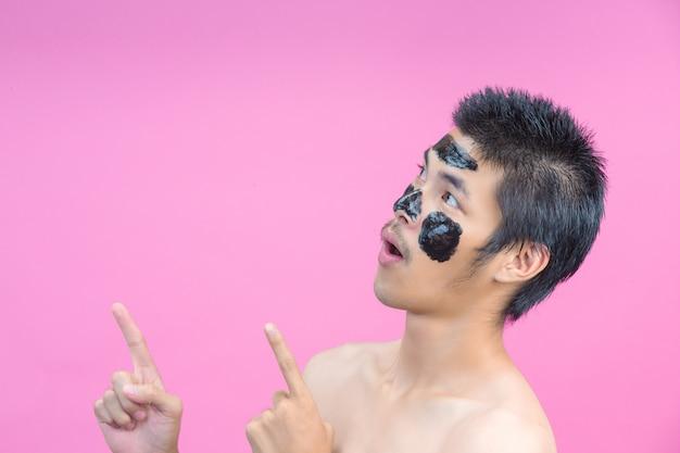 Homens bonitos que aplicam cosméticos pretos em seus rostos, mostrando várias posturas com um rosa.