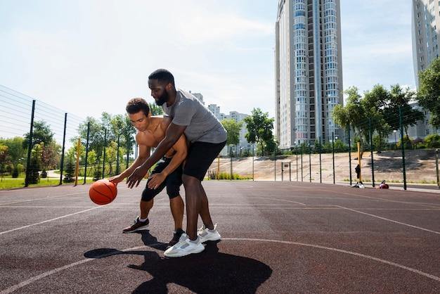 Homens bons treinando na quadra de basquete