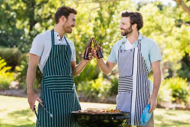 Homens brindando a garrafa de cerveja enquanto prepara churrasqueira