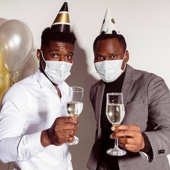 Homens brindando e usando máscaras médicas