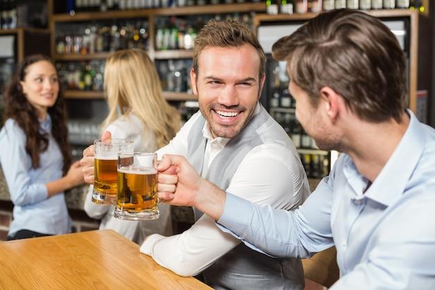 Homens brindando na frente, enquanto as mulheres falam por trás