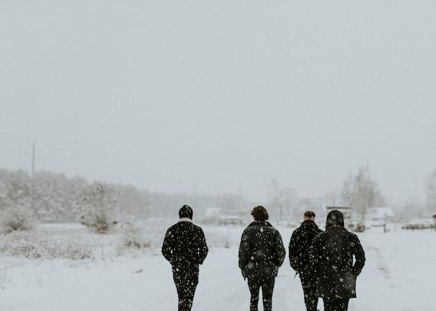 Homens caminhando por uma estrada cheia de neve