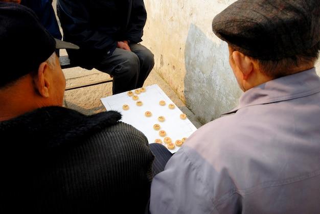 Homens chineses que apreciam um jogo da xadrez chinesa na rua.