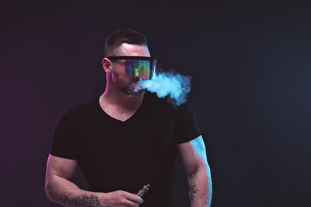 Homens com barba em óculos de sol vaping e libera uma nuvem de vapor
