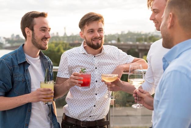 Homens com bebidas em uma festa no terraço