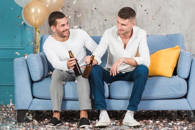 Homens com cerveja no sofá azul
