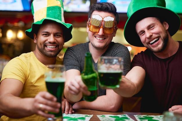 Homens com chapéu de duende e cerveja comemorando o dia de são patrício