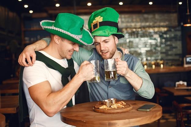Homens com chapéus verdes. amigos comemoram o dia de são patrício. celebração em um bar.