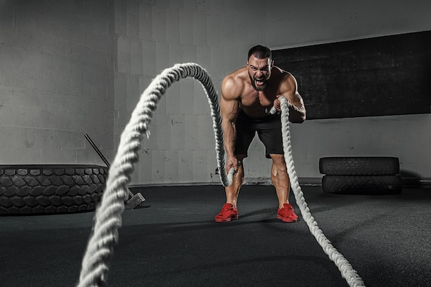 Homens com corda no ginásio de fitness treinamento funcional em treino