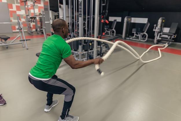 Homens com cordas de batalha de corda de batalha exercitam-se no ginásio de fitness.