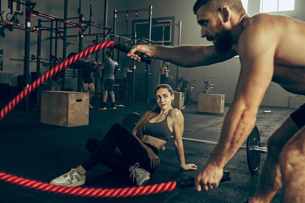 Homens com cordas de batalha exercem-se no ginásio de fitness. conceito crossfit. ginásio, esporte, corda, treinamento, atleta, treino, conceito de exercícios