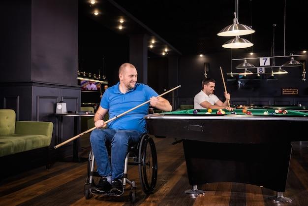 Homens com deficiência em cadeira de rodas jogam bilhar no clube