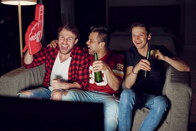 Homens com mão de espuma e cerveja em festa de futebol