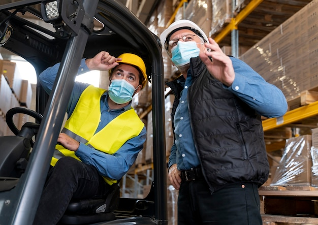 Homens com máscara trabalhando em armazém