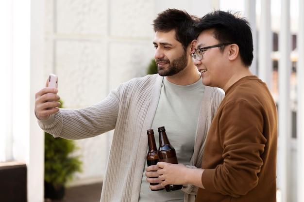Homens com tiro médio tirando selfies