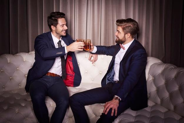 Homens com uísque brindando em clube de entretenimento