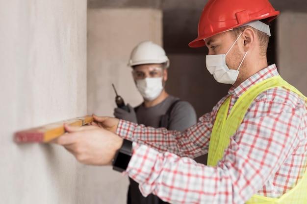 Homens com visão lateral trabalhando com máscaras