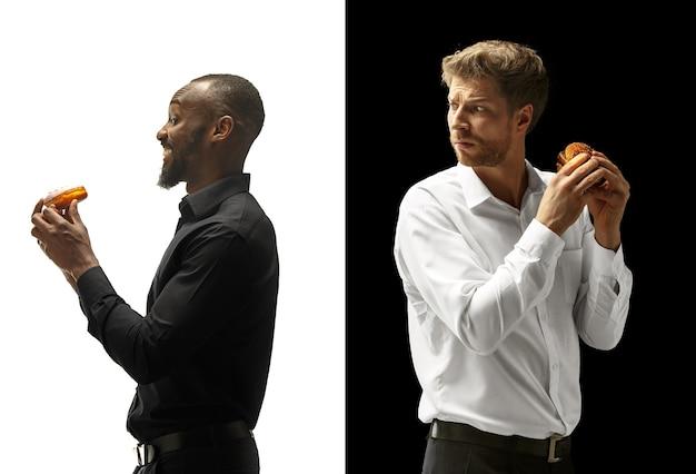 Homens comendo hambúrguer e donut em um espaço em preto e branco