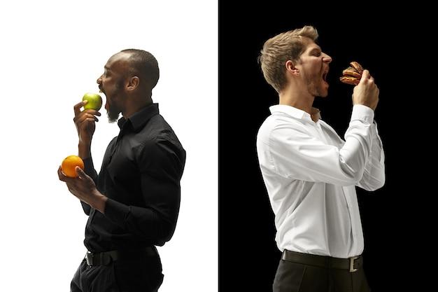 Homens comendo hambúrguer e frutas frescas em um espaço em preto e branco