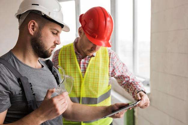 Homens construtores usando capacetes de segurança