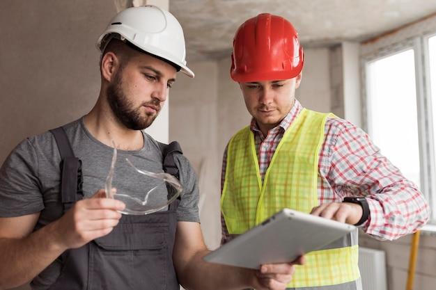Homens construtores usando capacetes