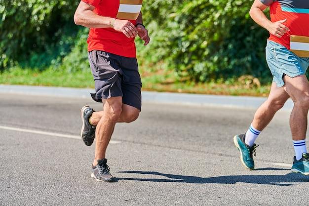 Homens correndo. homens esportivos correndo com roupas esportivas na estrada da cidade