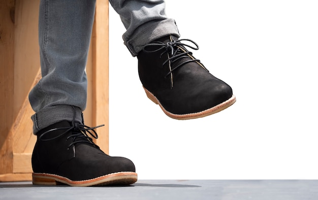 Homens da moda em jeans cinza e botins de couro preto.