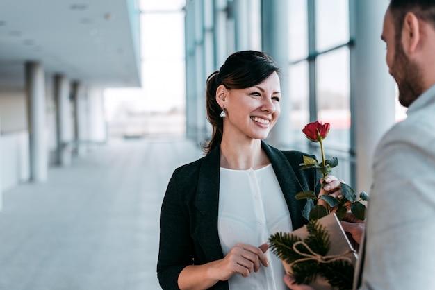 Homens dando uma rosa e um presente para o colega feminino.