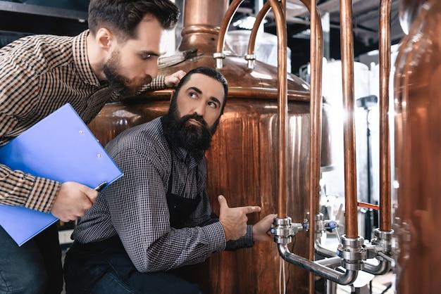 Homens de cervejeiros ansiosos verificam falha de equipamento.