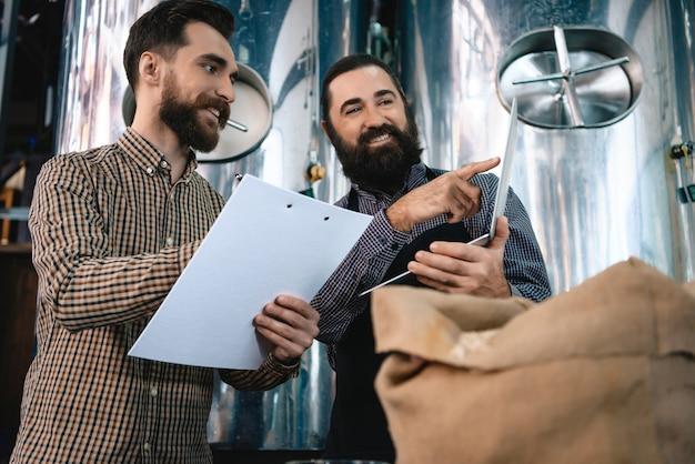 Homens de cervejeiros detém qualidade de cevada de verificação de laptop.