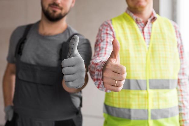 Homens de close-up segurando o polegar para cima