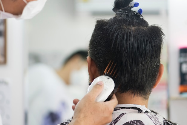 Homens de corte de cabelo barbearia. cabeleireiro masculino; barbeiros. barber corta a máquina do cliente para cortes de cabelo.