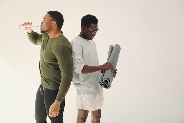 Homens de esportes em pé em uma parede branca