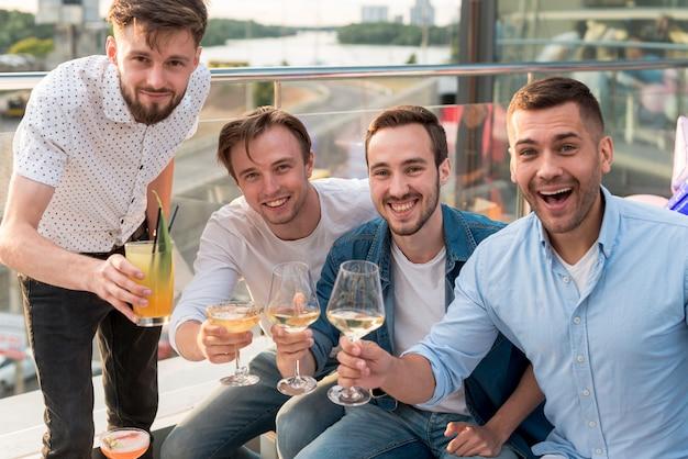 Homens de frente vista brindando em uma festa