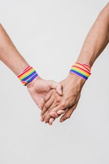 Homens de mãos dadas com fitas nas cores lgbt