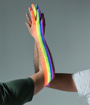 Homens de mãos dadas com o símbolo do orgulho