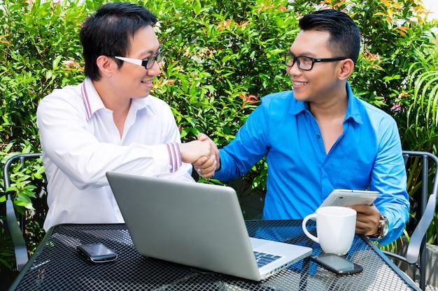 Homens de negócios asiáticos trabalhando ao ar livre