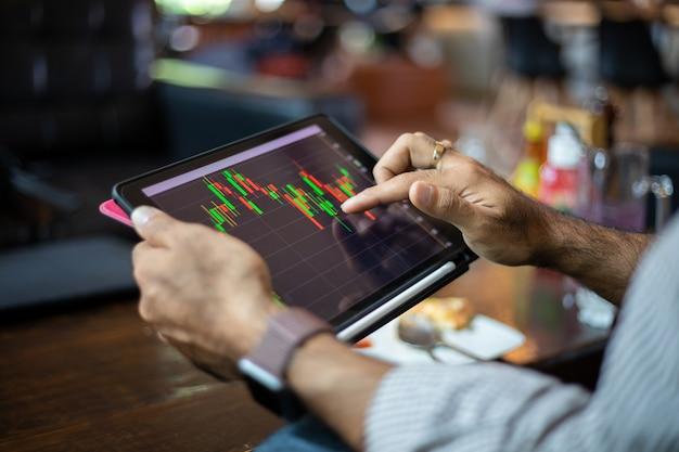 Homens de negócios asiáticos usando um tablet para trabalhar e verificar o gráfico de tendências de ações e análises financeiras em uma cafeteria