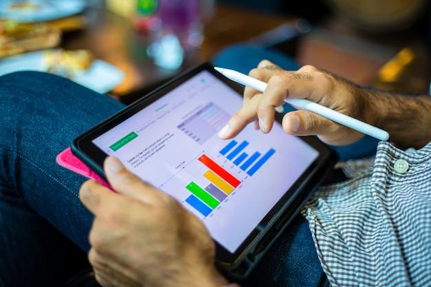 Homens de negócios asiáticos usando um tablet para trabalhar em uma cafeteria