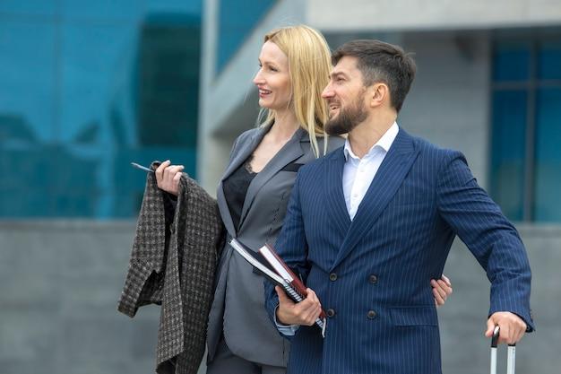 Homens de negócios bem-sucedidos parceiros, homem e mulher, no fundo de um edifício comercial com documentos nas mãos, discutindo projetos de negócios