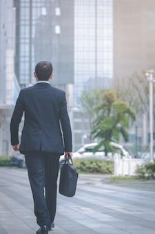 Homens de negócios carregam laptops no estacionamento