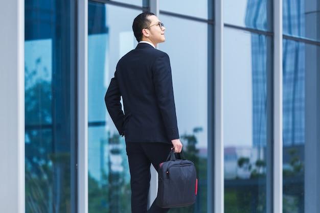 Homens de negócios carregam laptops para trabalhar na entrada de um prédio de escritórios