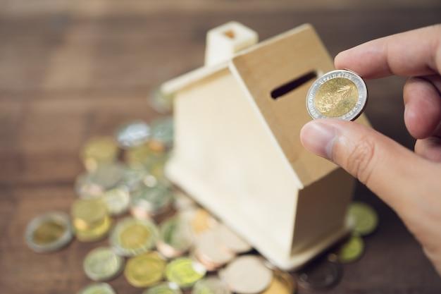 Homens de negócios coloque a moeda no cofrinho estilo casa para economizar dinheiro, economizar dinheiro