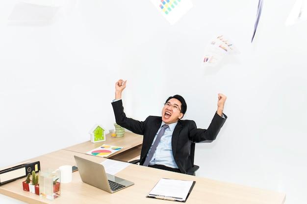 Homens de negócios com os braços levantados que cheering no escritório branco.