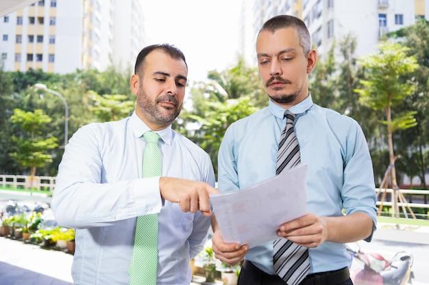 Homens de negócios concentrados que discutem o relatório ao andar