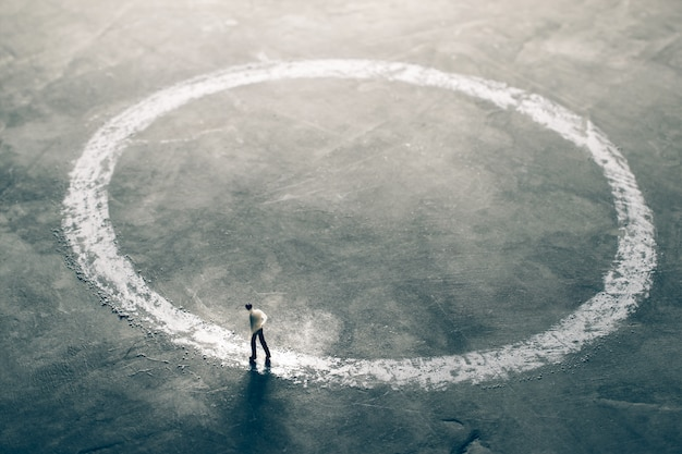 Homens de negócios de figura em miniatura, andando ao redor do lado de fora do círculo de giz encontrando o conceito de solução eficaz.